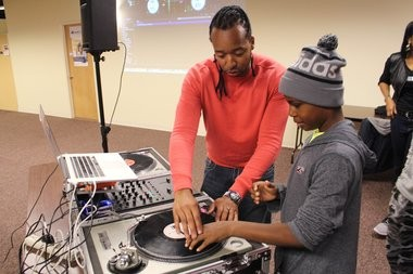 """Hasan Stephens, executive director of the Good Life Philanthropic Youth Foundation Inc., works with a young DJ at the South Side Innovation Center. Stephens is also known as """"DJ Maestro."""" Stephens also is an adjunct professor at SUNY Cortland. (Submitted photo)"""