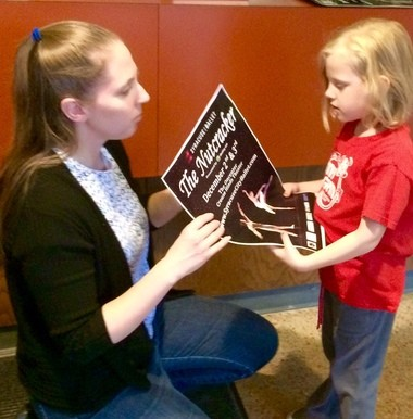 "Madeline Duffy, 5, shows her mother, Lynne, a poster for ""The Nutcracker."" The family will attend the sensory friendly performance Dec. 3 at 10 a.m."
