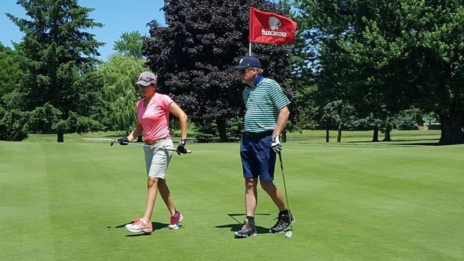 Tim Cahill (right) walks with his wife, Cara, off the green at Tuscarora Golf Club as Cara played 101 straight holes of golf June 21.