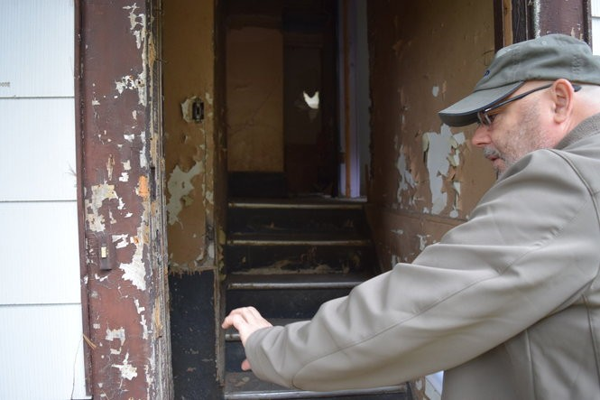 Pat Strodel, lead inspector for the testing firm LeadSafe, points out lead paint in the doorway at 1108 Hawley Ave., Syracuse. Home HeadQuarters intends to tear down the house and replace it with a modular home.