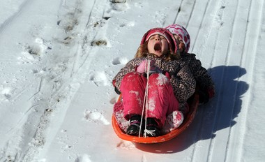 From the front, Rosemary and Connie Schimpff slide down a hill Sunday at the southern end of the Woodland Reservoir. The girls were there with their dad, Scott.