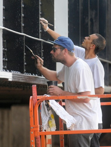 """In 2010, a team of artists put together by Steve Powers of Manhattan - including Mike Lee, of Syracuse, left, and Lew Blum, of Philadelphia - painted several murals on the West Street and West Fayette Street railroad bridges in Syracuse, including one that says: """"Now That We're Here No Where Else Matters"""" on Fayette Street. The sign painters were commissioned by the Near Westside Initiative."""