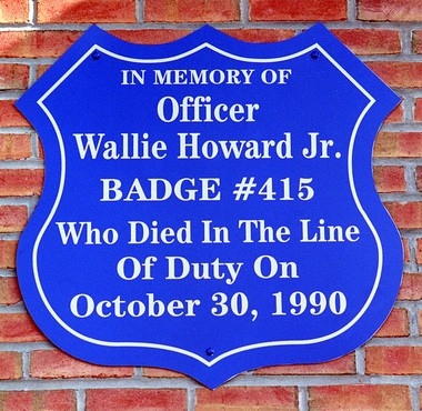 A plaque on the South Salina Street front, by the parking lot where Investigator Wallie Howard Jr. died.