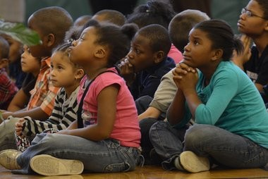 Van Duyn Elementary students, from left to right, Harmony Allison-Lemon, a kindergartener, Edith Hill, a first grader, Elijah Wright, a second grader, and Janae Robinson, a second grader, listen as Syracuse Police Chief Frank Fowler talks about Wallie Howard Jr., a Syracuse police officer who was killed 23 years ago.