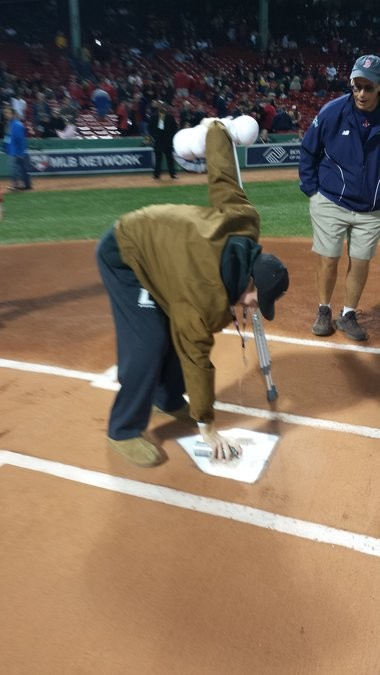 Pat Wiese spraypaints home plate before Game Two of the World Series at Fenway Park, while Dave Mellor, head Boston Red Sox groundskeeper, watches.