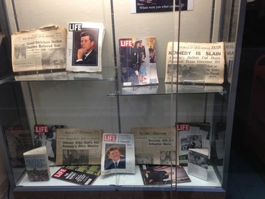 Display outside the DeWitt Community Library by Kelly Zajac Sickler, November 2013, ShoppingTown Mall; includes the front pages of the Syracuse daily newspapers after the assassination.