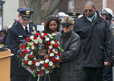 In 2010, on the 20th anniversary of the death of Investigator Wallie Howard, Jr., Syracuse Police Lt. John Kavanagh (left) assisted Delores Howard, Howard's mother, as she put down a wreath at the police memorial at Forman Park. In the background are Cyntia Howard (center) and Wallie Howard III (far right), Wallie's son and daughter.