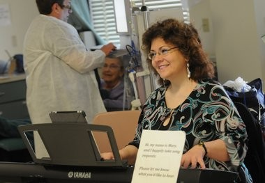 """Right, Symphoria's Mary Sugar plays the piano for patients receiving dialysis treatment at Northeast Medical Center. In the background, at left, is Melody Hutchinson, a nurse, talking with Carole Verne, a patient from Chittenango. """"I think it's wonderful,"""" Verne said about the music. """"It brings back a lot of memories."""""""