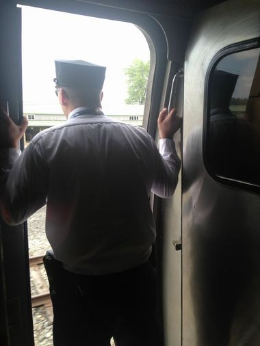 A conductor looks out the door as an Amtrak train pulls up to the New York State Fairgrounds.