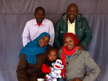 An example of a portrait taken by Kate Holmes, for Resettlement Services, and given as a gift at Christmas: Mahyeldeen and Nadya Musa (on right) with their infant son Mounir (center), Sudanese newcomers to Syracuse, with their longtime friends, Yagoub and Daresalaam Gamaas.
