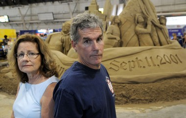 Elizabeth Berry of Syracuse (left) and Chris Burke of Onondaga (right) at the sand sculpture in the Center of Progress Building, 2011, at the New York State Fair. The sculpture honored the firefighters, police officers and other emergency workers who responded - often at the cost of their own lives - to the terrorist attacks of Sept. 11, 2001. Burke and Berry are siblings of Capt. Billy Burke Jr., who chose to stay in the north tower with two stranded civilians, including a man in a wheelchair.