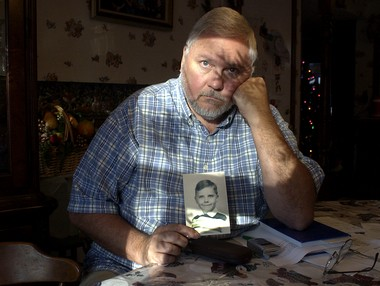 Charlie Bailey, in 2004, with a photo of himself as a 10-year-old: Voice of conscience for victims of abuse.