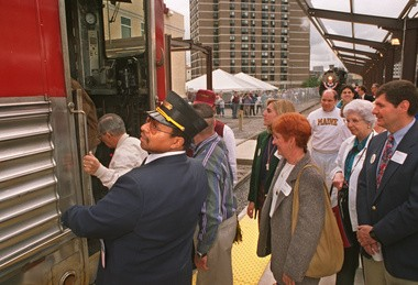 Conductor Bill Giles (left) assists passengers on the first official train ride on Ontrack, 1994.