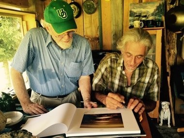 After John Francis McCarthy's journey to find pilot Bob Scianna, the pilot autographs a book that shows an iconic image of the Finger Lakes the two men captured, together.