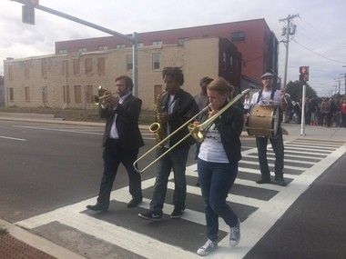 Melissa Gardiner (right) and her Second Line Syracuse jazz band lead schoolchildren, neighbors and civic officials across a new crosswalk at West Street.