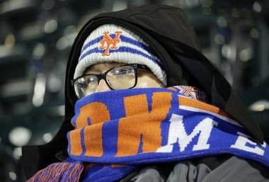 David Anaya, a fan, tries to keep warm during game two of the National League Championship Series between the Cubs and the Mets.