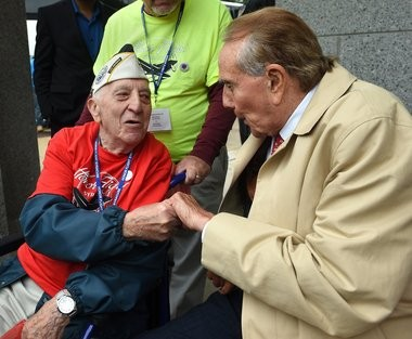 Ed Stone of Syracuse, a Pearl Harbor veteran who rode the Honor Flight last month to the National World War II Memorial in Washington D.C., talks with former Sen. Bob Dole just outside the gates. Dole, wounded in the war, often greets visiting veterans.