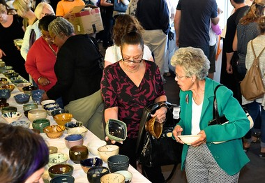 Marjorie Carter, of Syracuse, with friend Sandra Holmes, of Fayetteville, look over hundreds of bowls at the Empty Bowls Project of Syracuse, 2014.