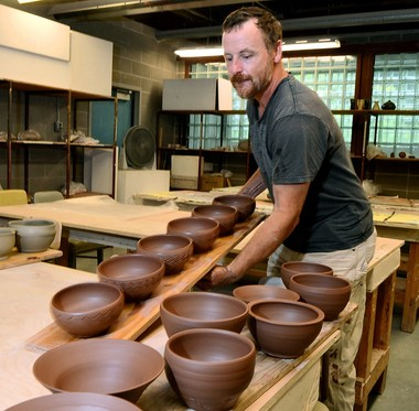 Errol Willett, Art Dept. Chairman and ceramics professor sets out newly made bowls to dry before they are fired in a kiln, September 10, 2011.