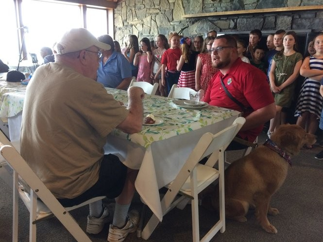 Justin Muir, 34, sits with his dog, Bella, during a recent Canteen Wednesday lunch at Clear Path for Veterans. Muir trained Bella to be a service dog to help him with his PTSD at Clear Path. Now he works there part-time and he brings Bella to lunch most Wednesdays. Teri Weaver | tweaver@syracuse.com