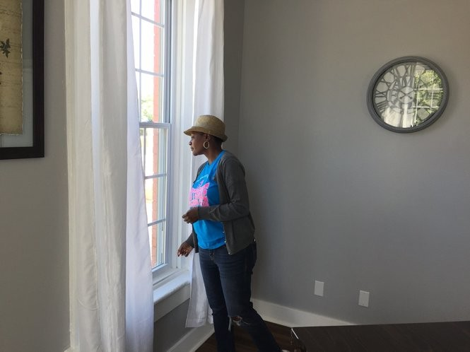 Camille Coakley looks out the window of an artist's loft that's above a cafe under construction on South Salina Street.