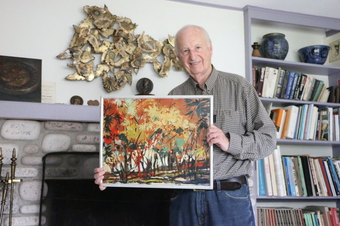 Painter Hall Groat holds up an early piece from his time in Korea.