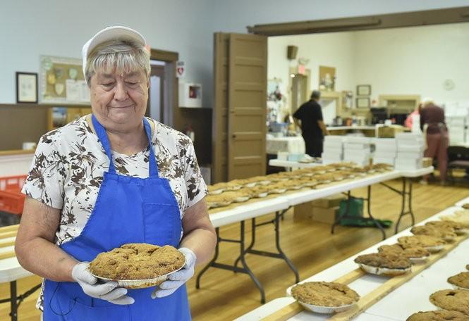Eva Palmer holds up an apple pie, one of a thousand made each fall by Columbian Presbyterian Church members. (Katrina Tulloch | ktulloch@syracuse.com)