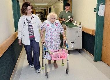 Heather Eckrich, a registered nurse, helps Nettie Jeffrey, 97, of Smyrna, walk along a hallway of Community Memorial Hospital in Hamilton.