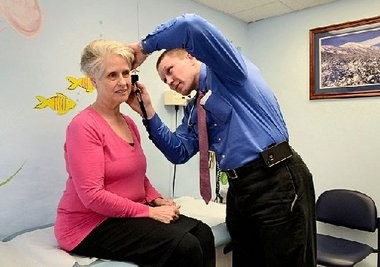 Dr. Daniel Rancier uses an otoscope to examine patient Sandra Lovell of Liverpool at the Christian Health Service