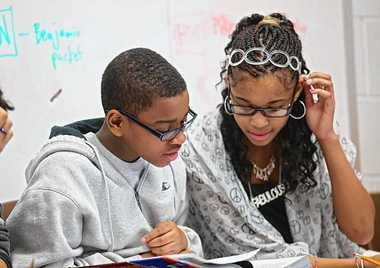 Kyilil Balaam, left, and Maiya White work together in Rich Richardson's social studies class at the Expeditionary Learning Middle school in Syracuse.