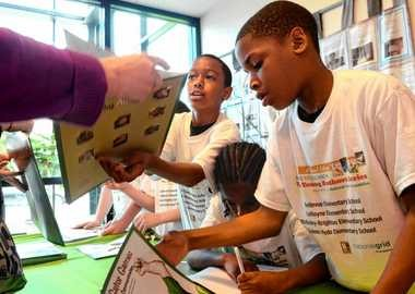 LeMoyne Elementary students Quinzell Williams, left, Khalil Davis, below, and Kwamere White sign books they helped write at a Say Yes event last year. Ellen M. Blalock / The Post-Standard