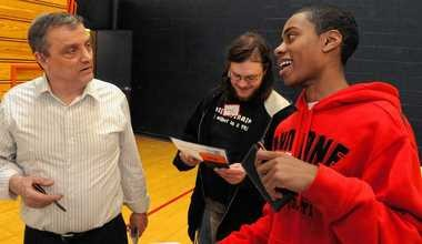 Jim Hartman of Focalpoint Credit Union, left, talks with Bradley Smith and Mante Roberson, right, in an economics class at Solvay High School in January.