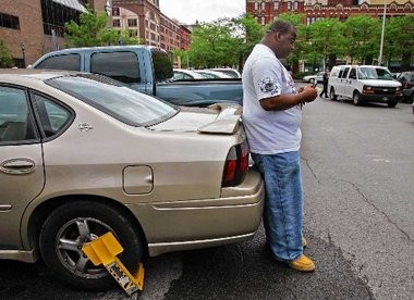 A Syracuse motorist makes a phone call after discovering a boot on his car in this 2008 file photo.