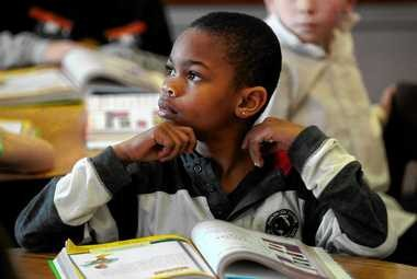 Second-grader Akil Young-William listens to his teacher, Rosa Trapasso, during a reading exercise at Porter Elementary School today.
