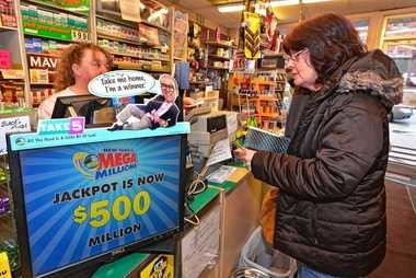 Georgia Anchikites, on right, buying a mega millions ticket from Lisa Gray, left, at Rocky's, Syracuse, NY.