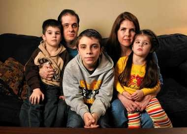 """Phil and Heather Ryder, of Syracuse, have opted out of having their children take state assessment tests. They have advised their 13-year-old son, Nikolas, middle, to write """"refused"""" across the top of his tests and read a book while others are taking the test in class. At left is Devin, 6, and at right is Kyla, 3."""