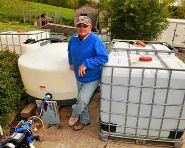 """Chris Sgouris and his """"tank farm"""" that provides water to his home on Amber Road in Marcellus after cow manure spread on a nearby field contaminated his well."""