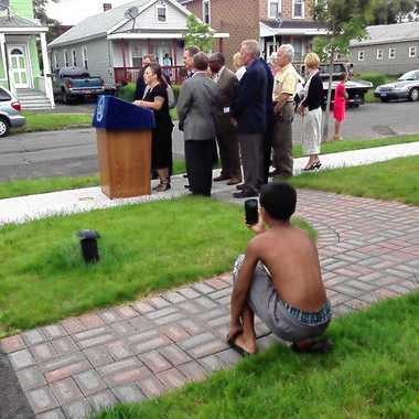 KyArie Rolon, 12, photographs the attorney general, the mayor, the county executive, two state senators, an assemblyman, city councilors and his mom Haydee Rolon in the family's front yard on Marcellus Street.