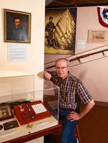 Dennis J. Connors , curator of history at the Onondaga Historical Association, with part of their current Civil War exhibit. The case in foreground contains medallion ribbons, hat emblem and shoulder strap insignia, and some minie bullets. On the wall in background is the first national colors flagstaff from the 149th New York Volunteer Infantry that was mended during the battle of Gettysburg and a portrait of Colonel Henry A. Barnum with the flag.