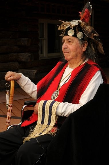 Onondaga Nation Chief Irving Powless Jr. with the Two Row Wampum in front of his log house at the Onondaga Nation