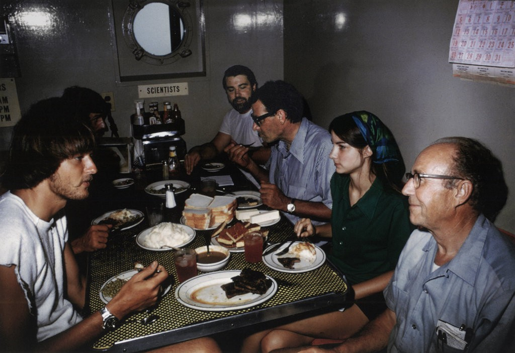 "Cathryn Newton in the mess hall of the Duke University research vessel, the Eastward, in Aug. 1973. To her left is MIT researcher Harold ""Doc"" Edgerton. Her father, John Newton, sits to her right."