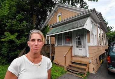 Nancy Lambertson stands outside of a Teall Avenue home where she lived in this 2009 file photo. Lambertson was one of 11 plaintiffs who sued Theresa Sanders and her company, Best Inc., in a dispute over rent-to-own housing. Lambertson alleged in 2009 that she paid Sanders nearly $2,000 after signing a contract to purchase the home, which was without a working furnace and with a shower connected to a garden hose instead of pipes. Authorities arrested Sanders this month on charges of scheme to defraud, grand larceny, residential mortgage fraud and falsifying business records.