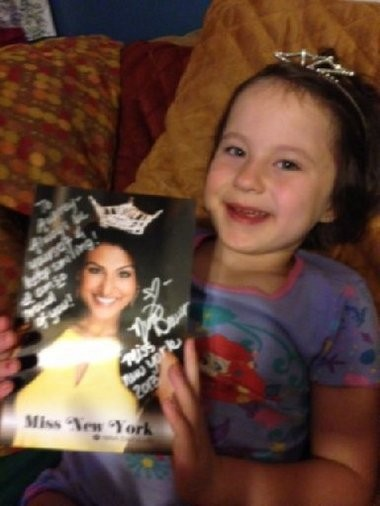 Six-year-old Aubrey Coyle shows off the autographed photo Nina Davuluri gave to her after Aubrey's mother, Amanda Coyle, allowed Davuluri to practice her Bollywood dance number in one of the back rooms at the East Area YMCA.