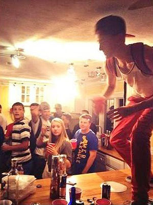 A teen stands on a kitchen counter as others watch in this photograph posted on Brian Holloway's Help Me Save 300 Facebook page.