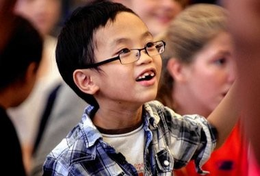 Third-grader Kevin Hoang, 8, listens to Frank Cammuso talk about this new book and who his favorite cartoonists are.