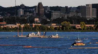 Dredging machines involved in the cleanup of Onondaga Lake float on the east side of the lake last month in front of the skyline of downtown Syracuse. While the dredging and capping operations get more attention, a smaller project is cutting mercury levels by 95 percent.