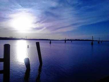 """The sun sets over Onondaga Lake. The view is from the northern end of the Onondaga Creekwalk, where the city of Syracuse plans to build """"Lake Lounge, """" a public access area with tiered decking."""