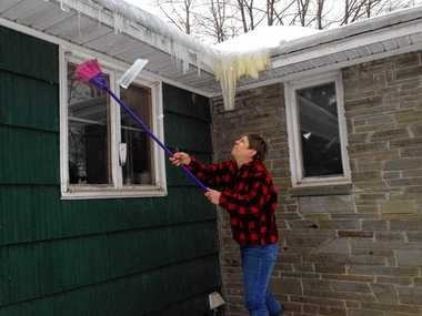 Janet Whidden breaks off icicles on her house of Armstrong Road in Syracuse today. Whidden is standing on a pile of snow scraped off from the roof earlier.
