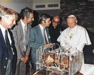 Pope John Paul II views a model of the Large Binocular Telescope that was to be built near Tucson, Ariz. Those meeting with him in Phoenix include Roger Angel, of the University of Arizona'As Steward Observatory (third from left), and the Rev. George Coyne, fourth from left. The Vatican Observatory Advanced Technology Telescope was a test bed for the LBT, as it proved the value of large, thin telescope mirrors made in a rotating furnace.