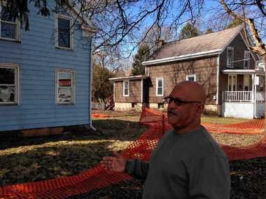 Oneida Mayor Max Smith stands outside two homes that were flooded last year and whose owners have abandoned them. Smith spoke today at SUNY Albany during a forum on severe weather in Upstate New York.